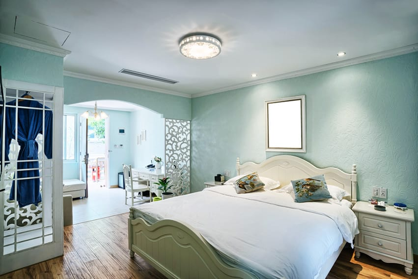 Light blue bedroom with large bed