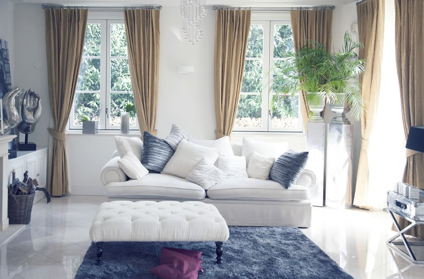 Living room with blue area rug, white couch and curtained windows