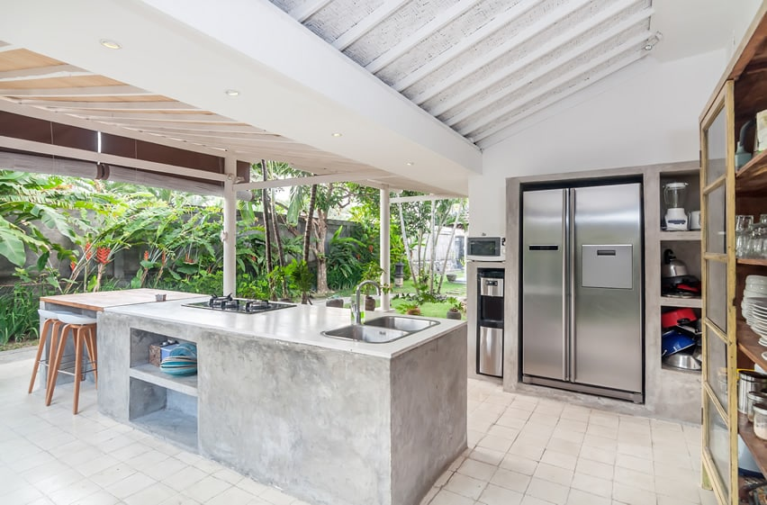 Outdoor kitchen with concrete counter and stainless steel fridge