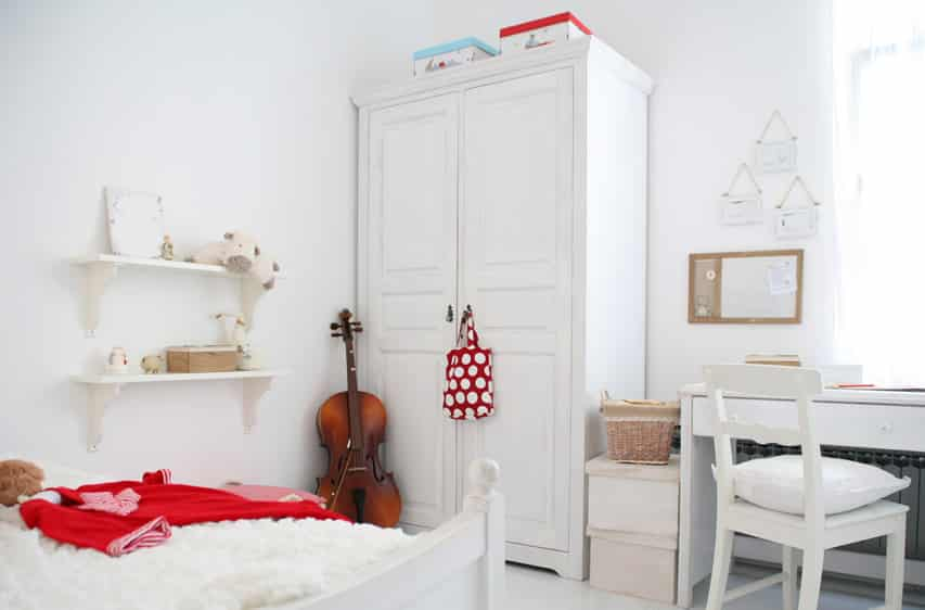 White wardrobe in bedroom with matching furniture