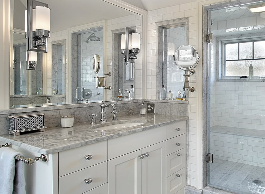 Bathroom with marble counter glass shower and white tile
