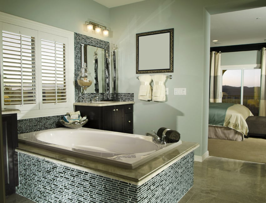 Master bath suite with bathtub with intricate tile work