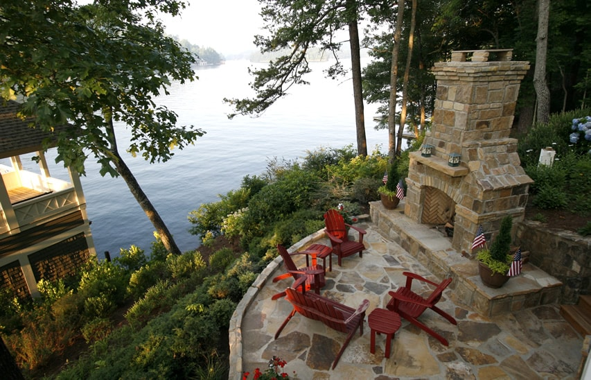 Beautiful outdoor fireplace seating area with lake view