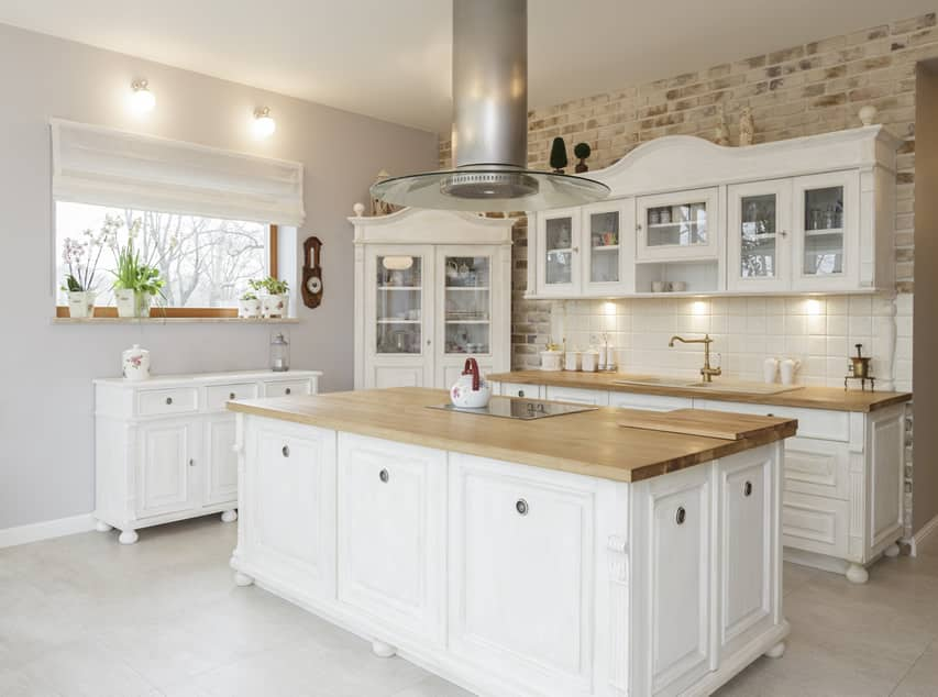 Custom white kitchen with wood butcher block counters and farmhouse style design.