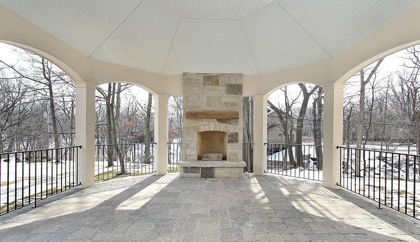 Large outdoor patio with fireplace and wrought iron railing