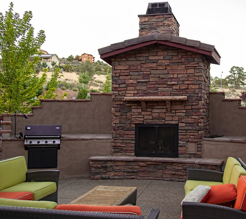 Large stone fireplace in back yard of home