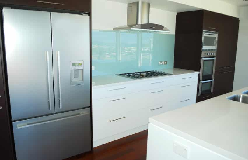 Light blue backsplash in modern kitchen with brown and white cabinets