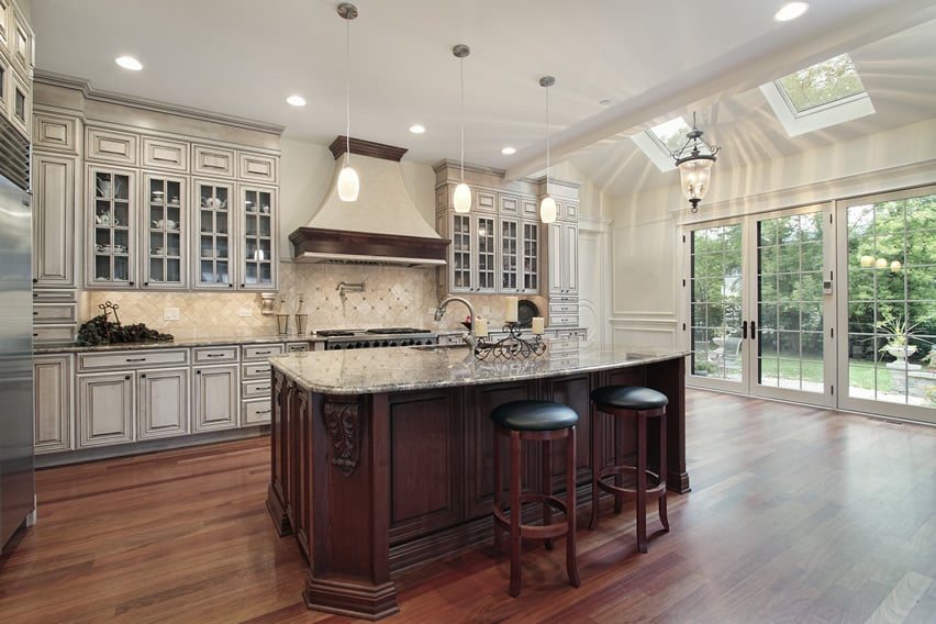 Luxury white kitchen with elegant glass faced cabinetry and wood flooring
