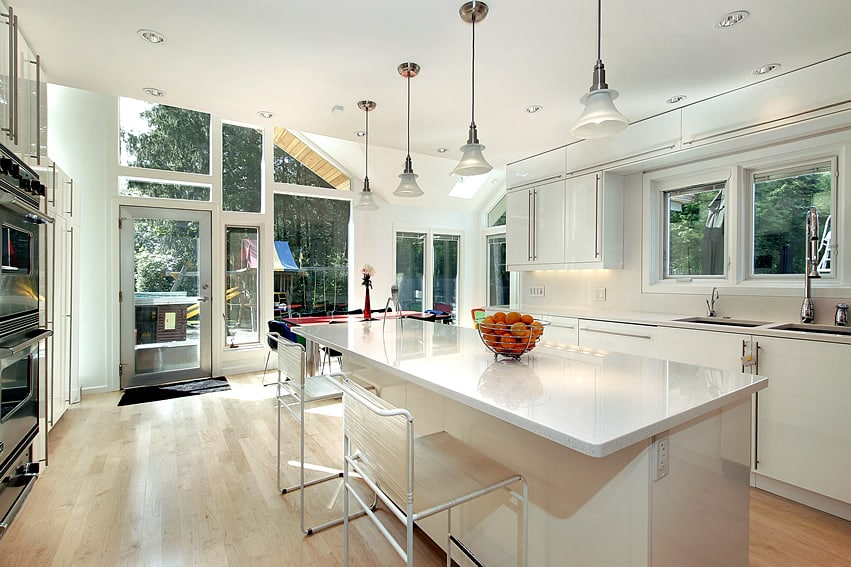 Open white kitchen design with wood flooring and glass door