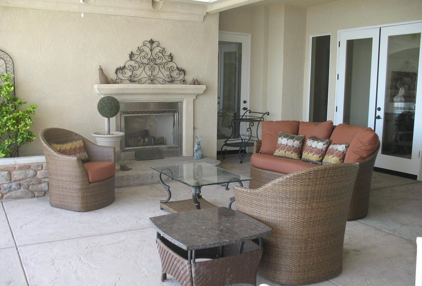 Outdoor fireplace with rattan furniture and glass table