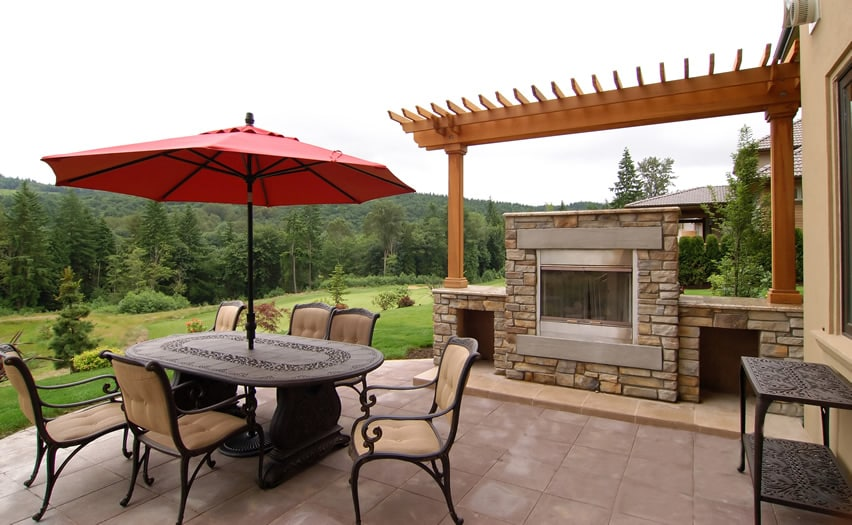 Outdoor fireplace with stone enclosure and pergola