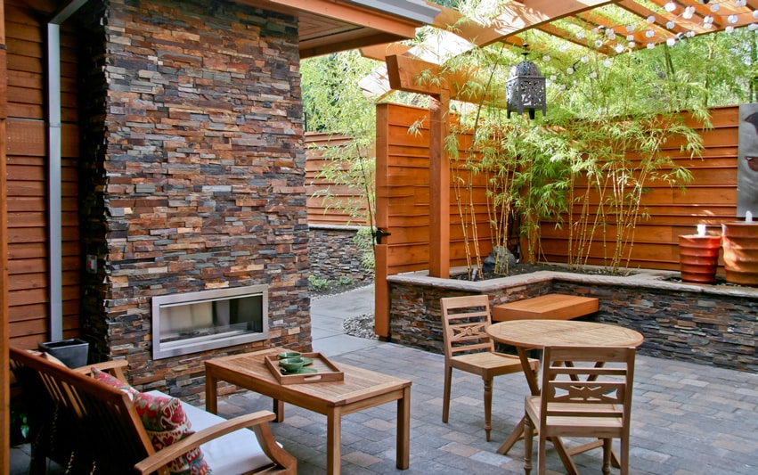 Outdoor slate fireplace with pergola on patio