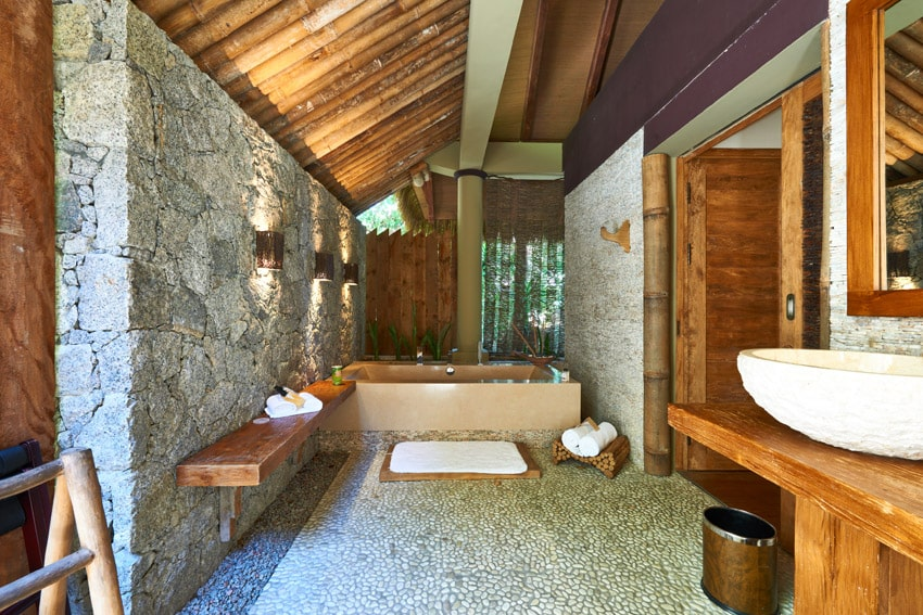 Rustic luxury bathroom with exposed stone wall