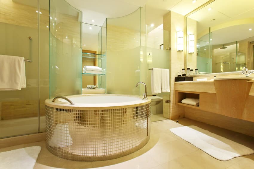 Shiny gold tile bathtub with glass shower area