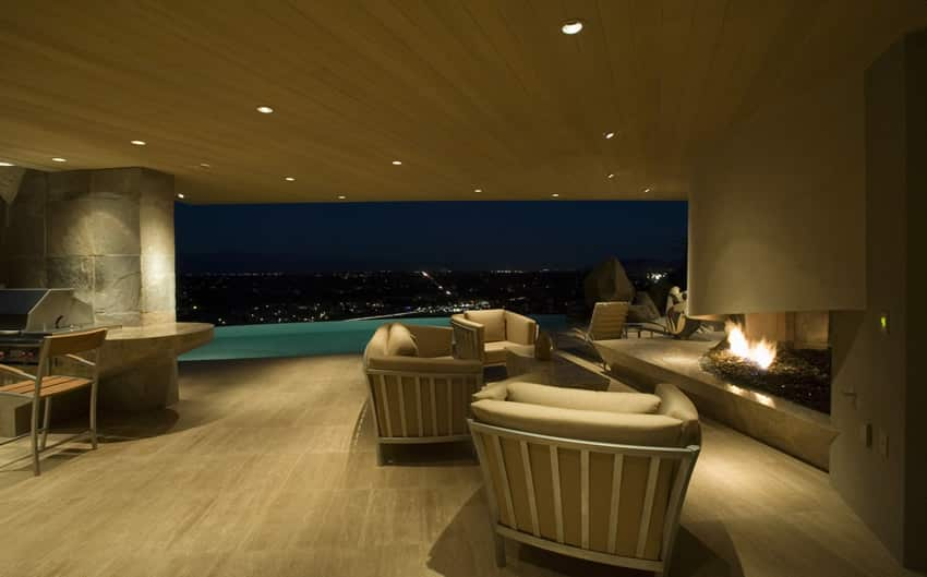 Stylish luxury patio with outdoor fireplace and city view