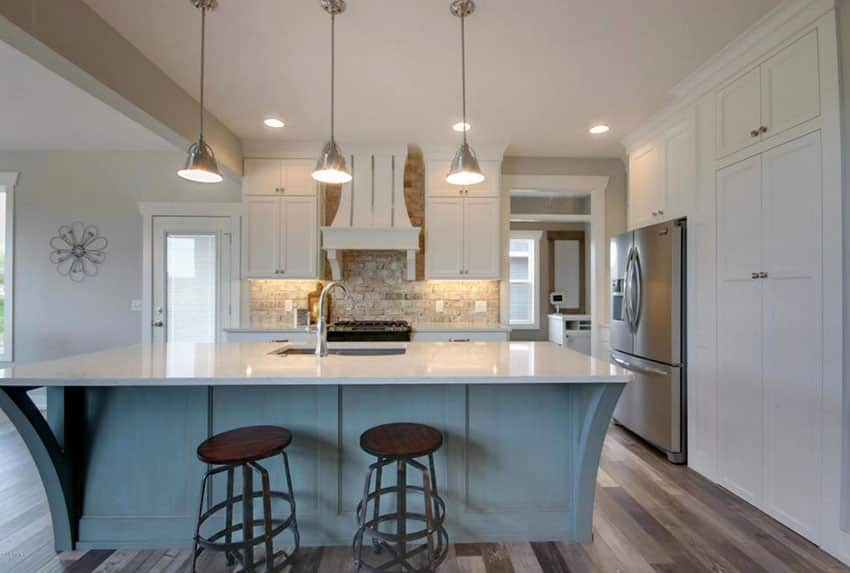 Traditional kitchen with white cabinets and blue painted island
