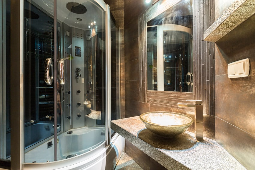 Ultra modern dark bathroom with curved shower enclosure and basin sink