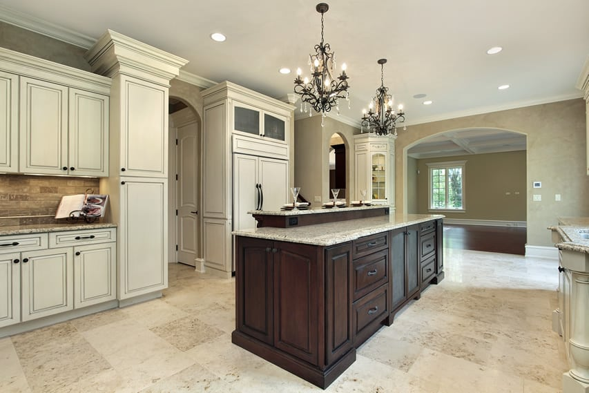 Upscale white kitchen with two chandeliers