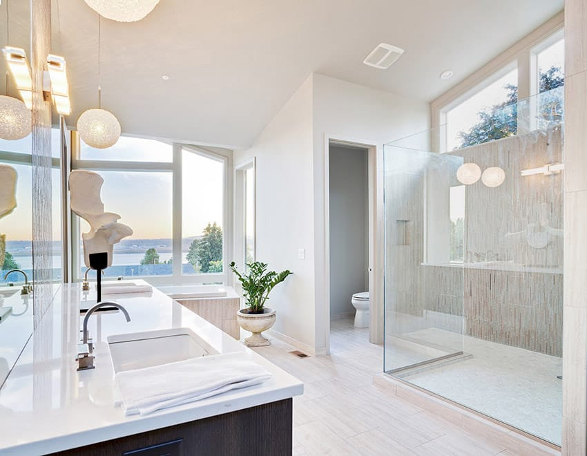 White bathroom with glass shower and globe lighting