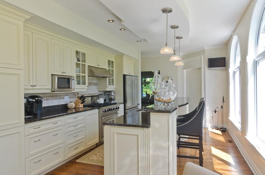 White kitchen with dark granite counter and eat in bar