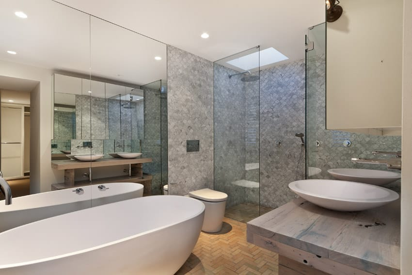 Bathroom with intricate tilework, large bathtub and basin sinks