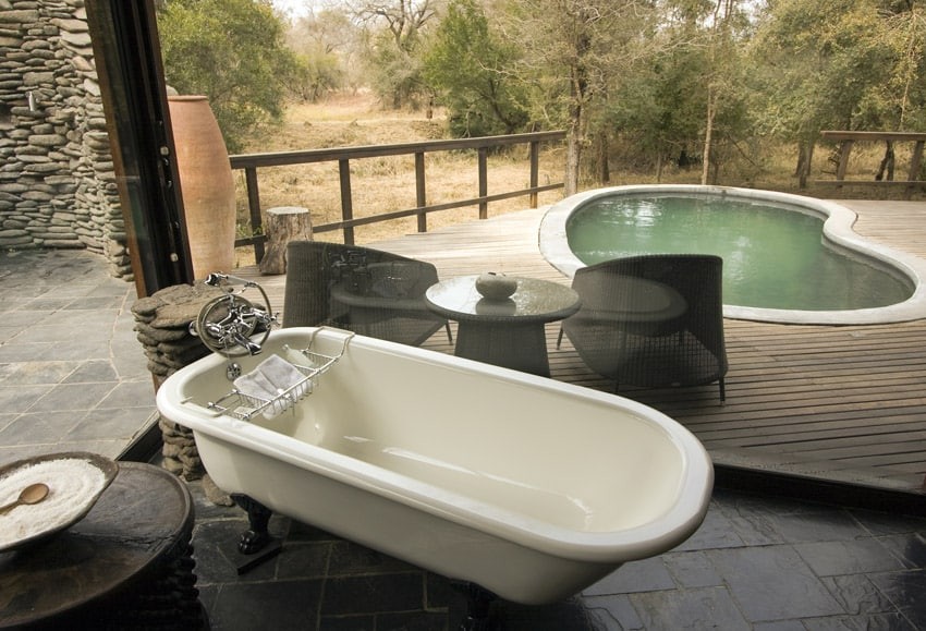 Bathtub overlooking private pool at African lodge