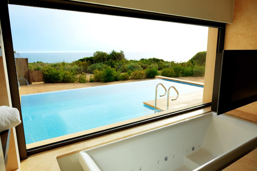 Jetted bathtub with pool and ocean view