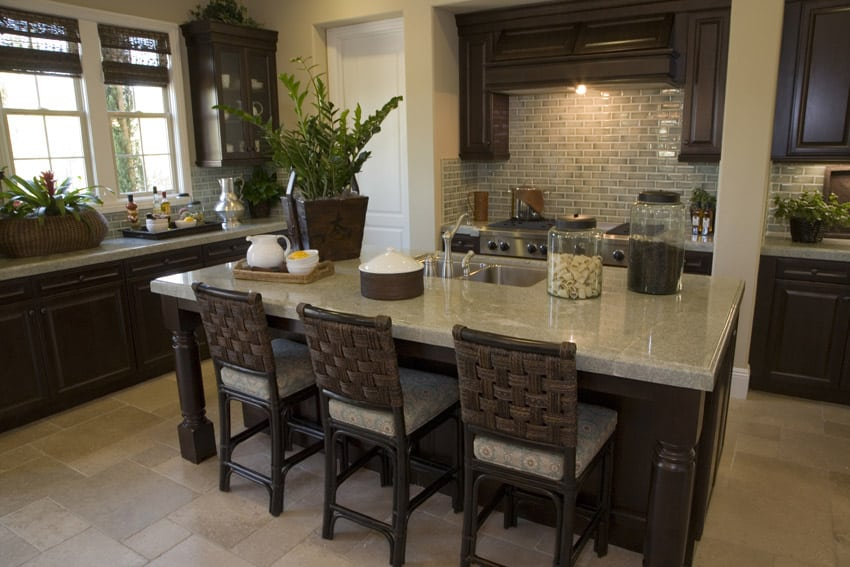 Dark wood cabinet kitchen with light granite counter and rattan bar stools
