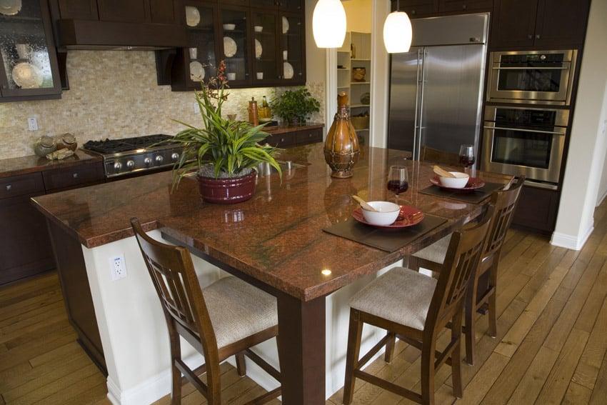 Dark wood kitchen with red granite counter