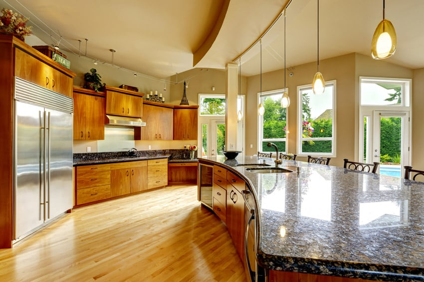 Designer kitchen with granite counters, wood flooring and curved island