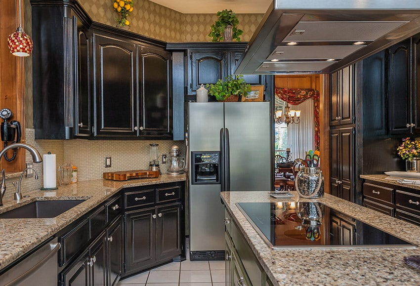 Kitchen with dark wood cabinetry beige granite counters