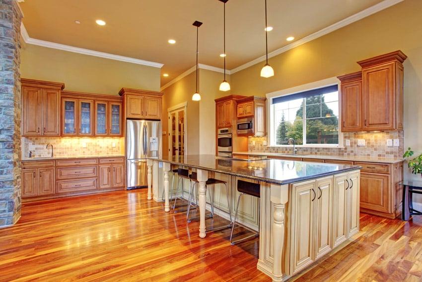 Kitchen with highly polished wood flooring white island