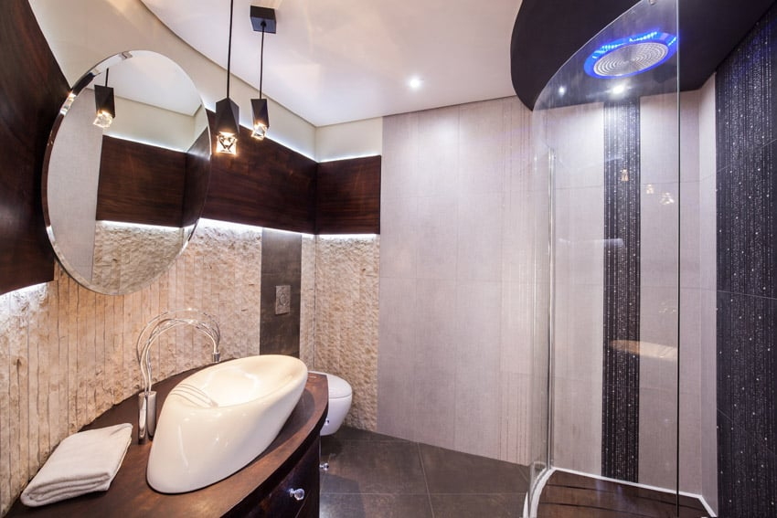 Modern shower in bathroom with round mirror
