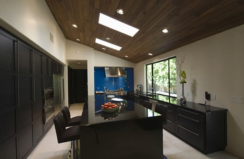 Modern wood kitchen with storage slanted ceiling and skylights