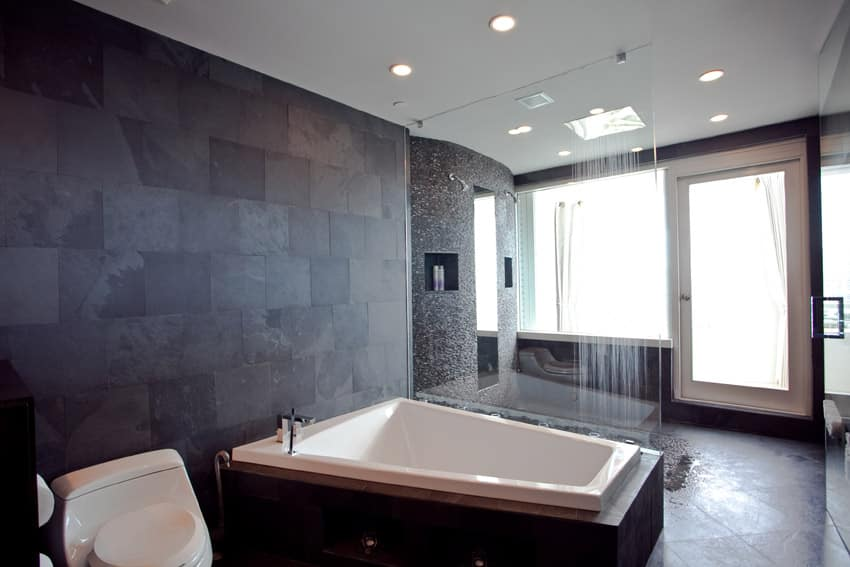 Resort style bathroom with dark accent wall and huge bathtub