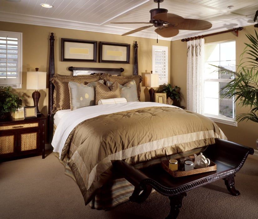 Richly decorated master bedroom with ceiling fan