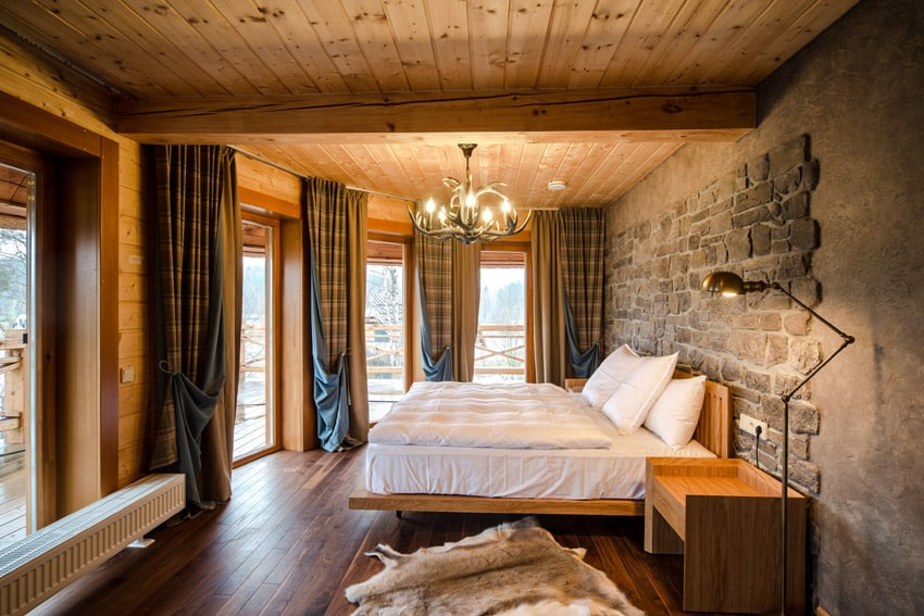 Rustic wood ceiling and stone accent wall in master bedroom