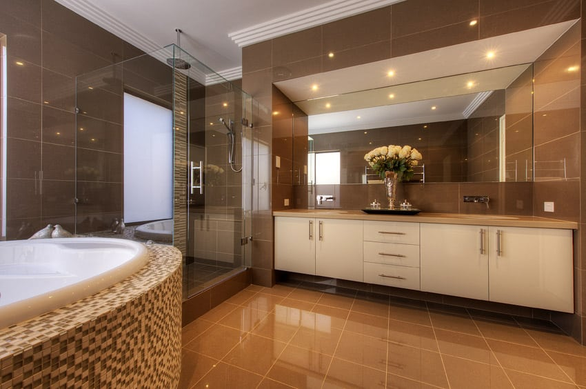 Sleek contemporary bathroom design in brown with tiled jacuzzi tub