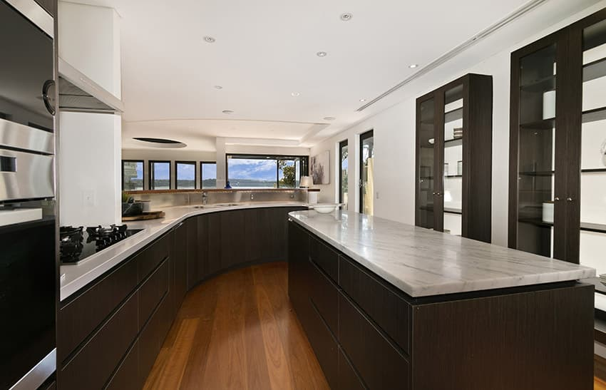 Upscale modern dark wood kitchen with white counters