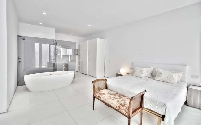 White master bedroom with bathtub in room