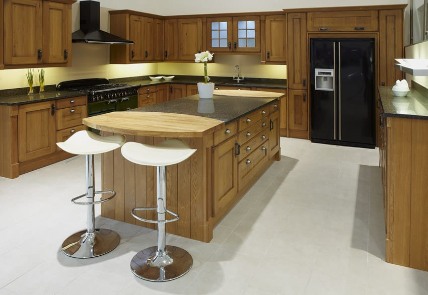 Wood kitchen with black appliances and wood counter island