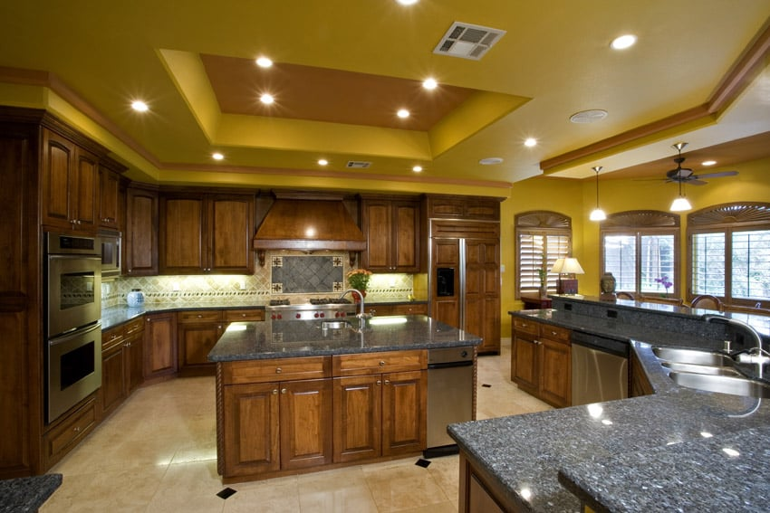 yellow ceiling kitchen with rich wood cabinetry and two level granite