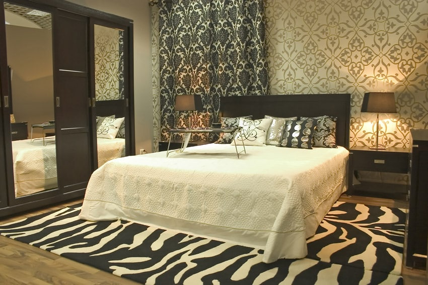 Master bedroom with patterned wallpaper and zebra area rug