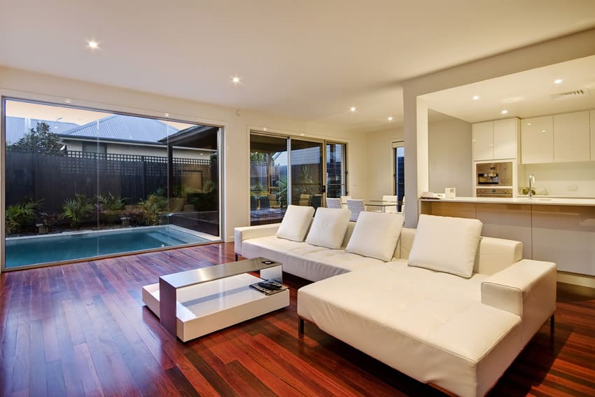 Beautiful wood flooring in living room with view of backyard pool