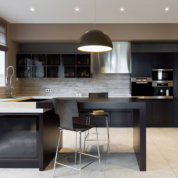 Black modern kitchen with large light fixture