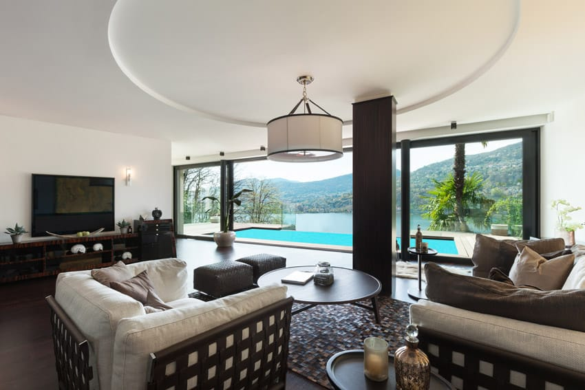 Living room with pool view and circular tray ceiling