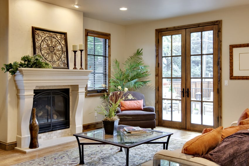 Living room with white fireplace and wood frame windows and door