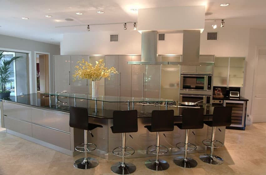Modern kitchen with long dining island and chrome and leather bar stools