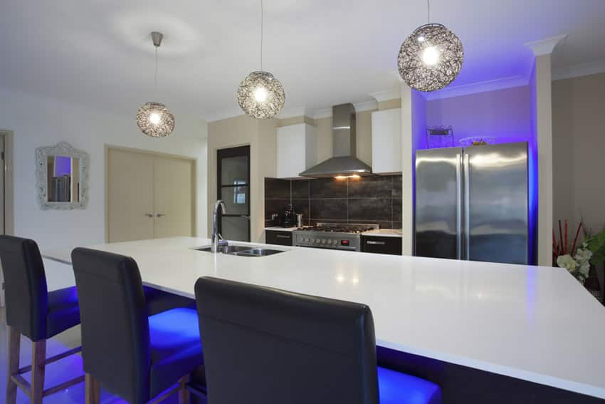 Modern kitchen with large island, wire globe lighting, and neon backlights.