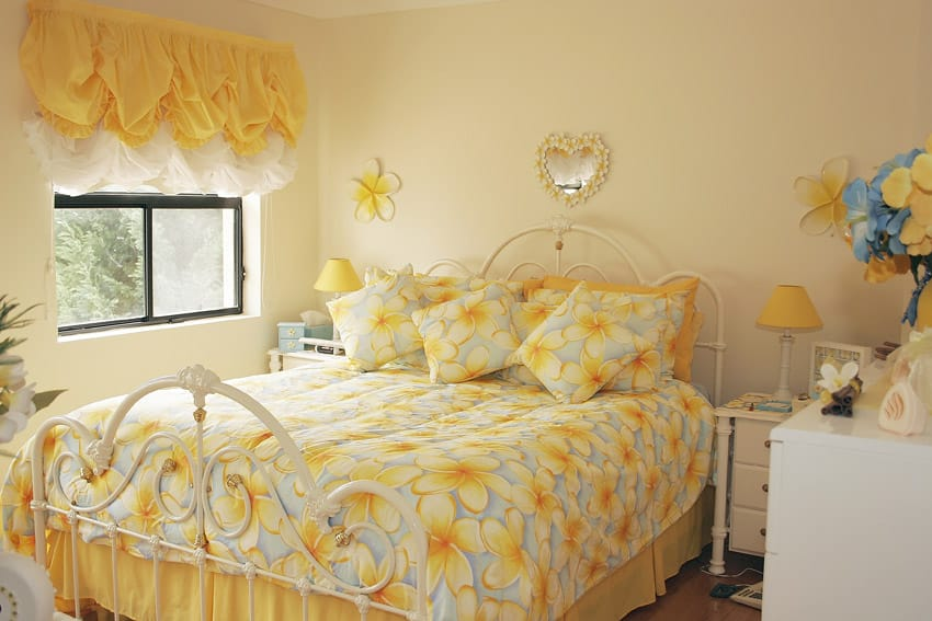 Bright yellow girls bedroom with decorative metal bed frame